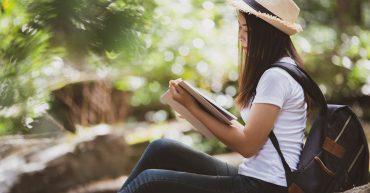 Beautiful woman reading book at nature